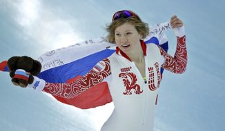 Silver medallist Russia's Olga Fatkulina holds her national flag and celebrates after the women's 500-meter speedskating at the Adler Arena Skating Center during the 2014 Winter Olympics, Tuesday, Feb. 11, 2014, in Sochi, Russia. (AP Photo/David J. Phillip )