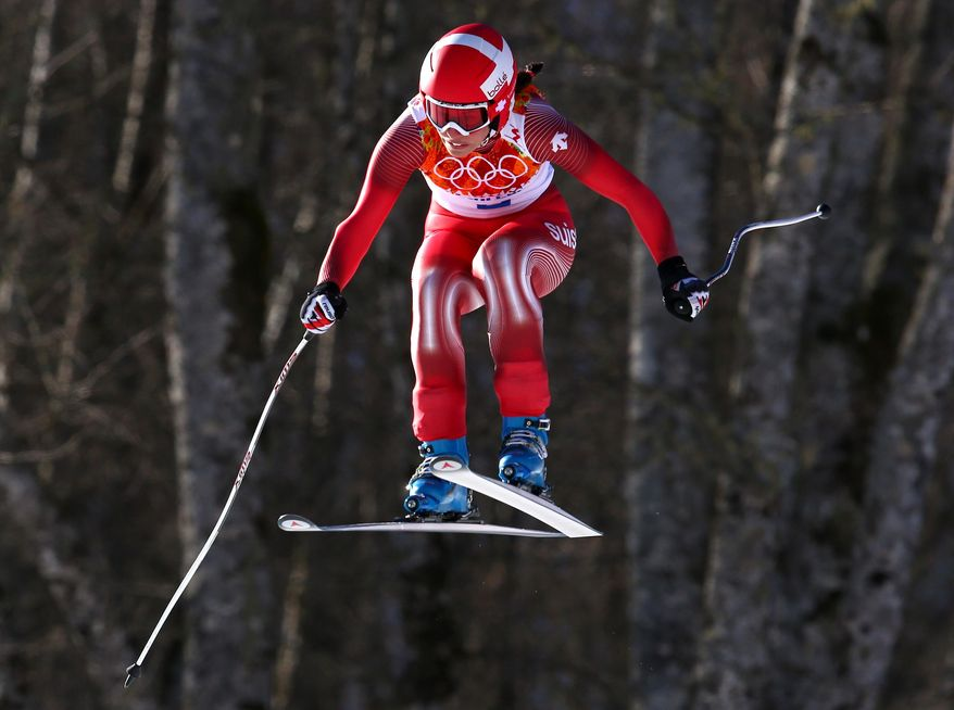 Switzerland's Dominique Gisin makes a jump in the women's downhill at the Sochi 2014 Winter Olympics, Wednesday, Feb. 12, 2014, in Krasnaya Polyana, Russia. (AP Photo/Alessandro Trovati)