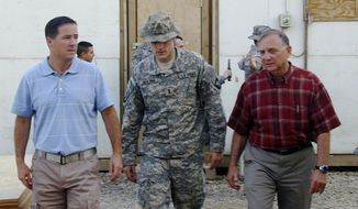 FILE - In this Sept. 21, 2008 file photo 1st Lt. Michael C. Behenna, center, walks out the courtroom flanked by his defense attorneys in Camp Speicher, a large U.S. base near Tikrit, north of Baghdad, Iraq. Behenna of Edmond, Okla., who was convicted of killing an Iraqi prisoner has been granted parole after serving five years of a 15-year sentence, the Army said Wednesday, Feb. 12, 2014. (AP Photo/Vanessa Gera, File)