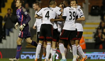 Fulham's players celebrate an own goal by Liverpool's Kolo Toure during their English Premier League soccer match at Craven Cottage, London, Wednesday, Feb. 12, 2014. (AP Photo/Sang Tan)