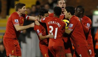 Liverpool's players celebrate Philippe Coutinho's goal against Fulham during their English Premier League soccer match at Craven Cottage, London, Wednesday, Feb. 12, 2014. (AP Photo/Sang Tan)