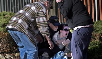 An official comforts the mother, of a two year old child that was killed at Wood Mark Apartments, Wednesday, Feb. 12, 2014 in Tacoma, Wash. A Tacoma-area man called 911 and said he had killed his 2-year-old daughter and was going to kill himself, authorities said Wednesday. Pierce County deputies rushed to the Woodland Park apartments around 11 a.m. and found the girl dead and the 26-year-old man semiconscious with a binding around his neck, said sheriff's spokesman Ed Troyer. (AP Photo/The News Tribune, Lui Kit Wong)