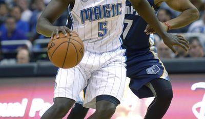 Orlando Magic shooting guard Victor Oladipo (5) drives past Memphis Grizzlies point guard Darius Morris during the first half of an NBA basketball game in Orlando, Fla., Wednesday, Feb. 12, 2014. (AP Photo/Phelan M. Ebenhack)