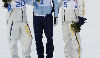 Norway's gold medal winner Ola Vigen Hattestad is flanked by Sweden's silver medal winner Teodor Peterson, left, and Sweden's  bronze medal winner Emil Joensson during the flower ceremony of the men's cross-country sprint final at the 2014 Winter Olympics, Tuesday, Feb. 11, 2014, in Krasnaya Polyana, Russia.(AP Photo/Matthias Schrader)