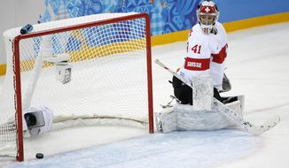 Goalkeeper Florence Schelling of Switzerland looks back at the puck after Jenni Hiirikoski's of Finland scored during the first period of the 2014 Winter Olympics women's ice hockey game at Shayba Arena, Wednesday, Feb. 12, 2014, in Sochi, Russia. (AP Photo/Petr David Josek)