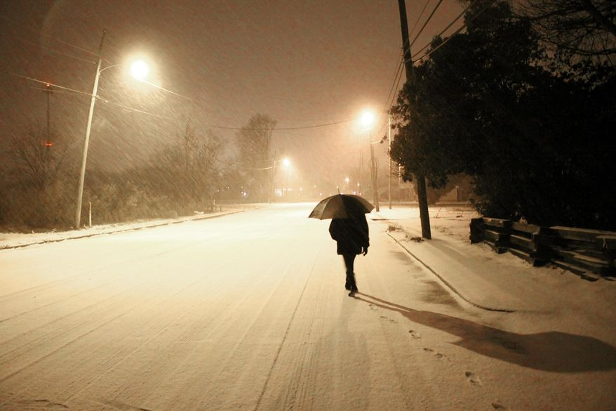 Rosemary Bennett walks home Tuesday, Feb. 11, 2014, during a winter storm in Greenville, Miss. (AP Photo/The Delta Democrat-Times, Bill Johnson) ** FILE **