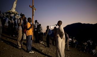 In this Feb. 9, 2014 photo, Rev. Jules Campion leads a procession of Christian pilgrims carrying a statue of Our Lady of Fatima in the village of Bois-Neuf, Haiti. Christian pilgrims came to the barren mountainside in central Haiti seeking favors and spiritual renewal. (AP Photo/Dieu Nalio Chery)
