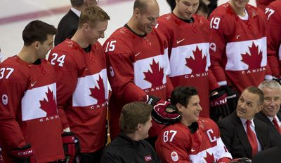 Team Canada's Patrice Bergeron (37), Corey Perry (24), Rick Nash (61), Jay Bouwmeester (19), head coach Mike Babcock, front left, General Manager Steve Yzerman and Bob Nicholson, far right front,  look on as Ryan Getzlaf tickles Sidney Crosby's ear as players wait for a team photo at the start of practice at the Sochi Winter Olympics Tuesday Feb. 11, 2014, in Sochi, Russia. (AP Photo/The Canadian Press, Adrian Wyld)