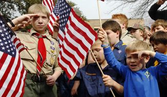 """Boy Scouts salute as they recite the pledge of allegiance during the """"Save Our Scouts"""" prayer vigil and rally against allowing gays in the organization in front of the Boy Scouts of America National Headquarters in Dallas on Feb. 6, 2013. (Associated Press) **FILE**"""