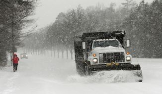 A truck plows a road in Charlotte, N.C., Wednesday, Feb. 12, 2014, as a winter storm moves into the area. (AP Photo/Chuck Burton)