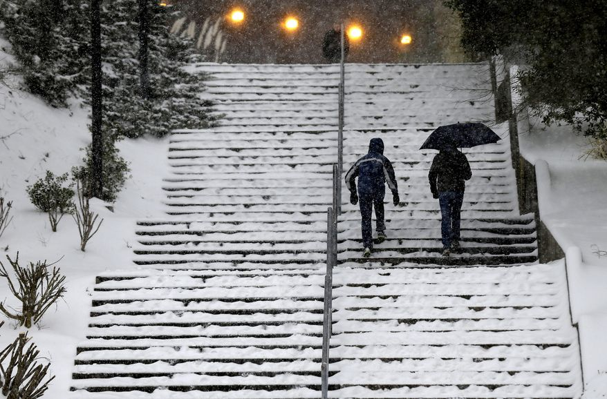 Pedestrians maneuver a stairway outside the Dean E. Smith Center at the University of North Carolina prior to a basketball game between North Carolina and Duke in Chapel Hill, N.C., Wednesday, Feb. 12, 2014. (AP Photo/Gerry Broome) ** FILE **