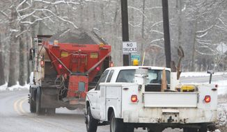 A Fort Payne Public Works truck sands a section of Jeff Cook Parkway atop Lookout Mountain Wednesday Feb. 12,  2014 in Fort Payne Ala.   A winter storm warning covered almost the entire northern half of the state, and many schools and businesses were closed or opened late.  (AP Photo/Hal Yeager)
