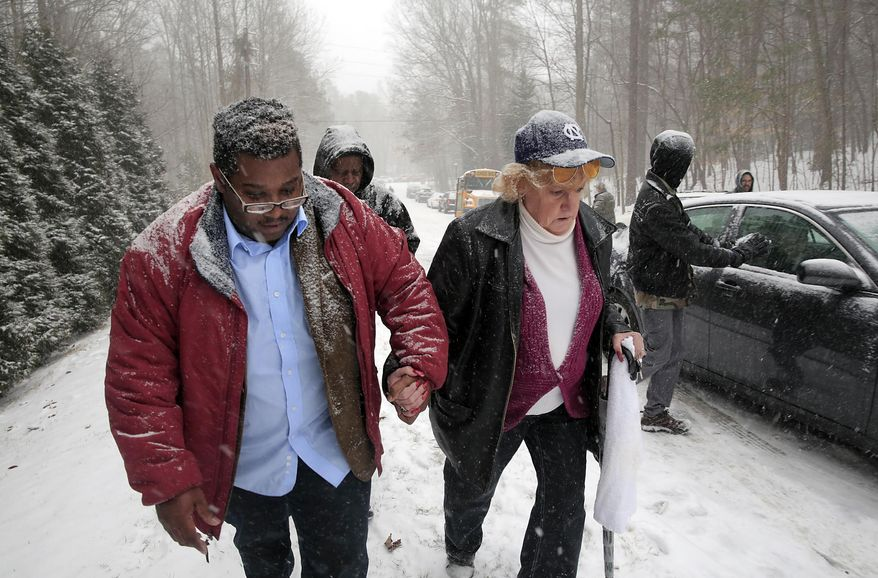 School bus driver Derese Burnette, left, holds the hand of fellow school bus driver Joan Thompson while assisting Thompson up a slick hill after their school buses got stuck in Chapel Hill, N.C., during a snow storm on Wednesday, Feb. 12, 2014.   second winter storm in two weeks pummeled South Carolina on Wednesday prompting Gov. Nikki Haley to ask President Barack Obama to declare the state a federal disaster area.  (AP Photo/Ted Richardson)