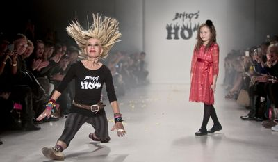 Fashion designer Betsey Johnson lands into a split while doing acrobatics on the runway as her granddaughter looks on after showing her Fall 2014 collection, during New York Fashion Week on Wednesday Feb. 12, 2014.  (AP Photo/Bebeto Matthews)