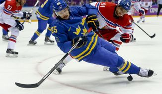 Sweden defenseman Erik Karlsson (65) loses his footing as he passes the puck from Czech Republic forward Martin Erat in the first period of a men's ice hockey game at the 2014 Winter Olympics, Wednesday, Feb. 12, 2014, in Sochi, Russia. (AP Photo/Mark Humphrey)