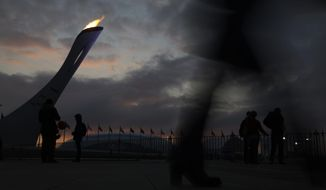 Spectator walk past the Olympic Cauldron as the sun sets at the 2014 Winter Olympics, Tuesday, Feb. 11, 2014, in Sochi, Russia. (AP Photo/Morry Gash)