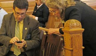 Kansas state Rep. Jim Howell, left, a Derby Republican, confers with Patricia Stoneking, president of the Kansas State Rifle Association, during a House committee discussion of gun-rights legislation, Wednesday, Feb. 12, 2014, at the Statehouse in Topeka, Kan. Howell is the main legislative advocate of the bill, and Stoneking's group is backing it. (AP Photo/John Hanna)