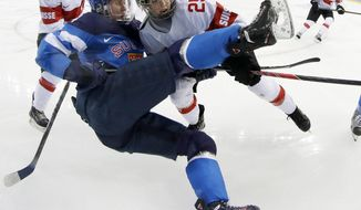 Rosa Lindstedt of Finland gets tangled up with Alina Muller of Switzerland near the boards during the third period of the 2014 Winter Olympics women's ice hockey game at Shayba Arena, Wednesday, Feb. 12, 2014, in Sochi, Russia. (AP Photo/Matt Slocum)