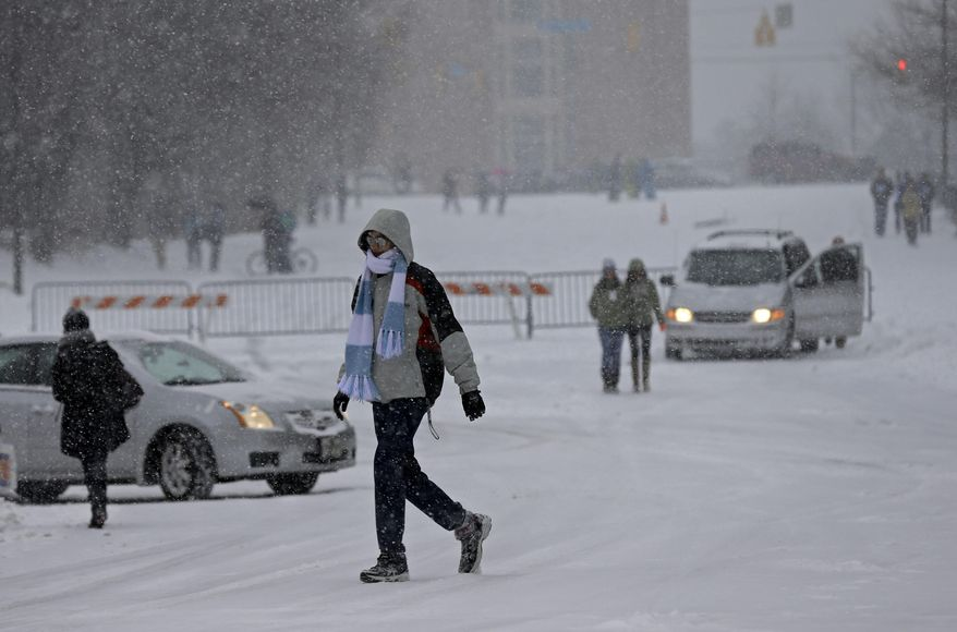 Students make their way through the falling snow on campus at the University of North Carolina in Chapel Hill, N.C., Wednesday, Feb. 12, 2014. The National Weather Service has issued a winter storm warning for Wednesday and into Thursday covering most of North Carolina. (AP Photo/Gerry Broome)