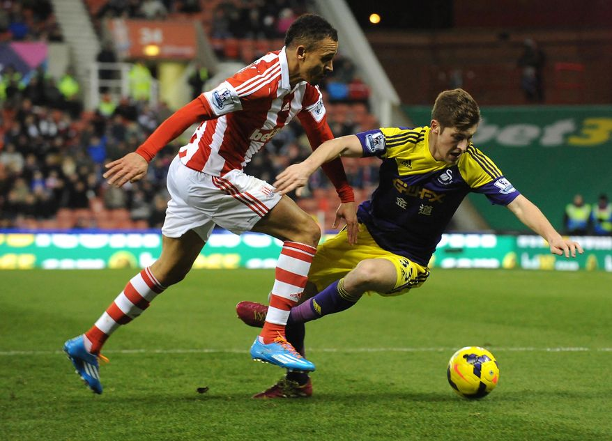 Stoke's Peter Odemwingie competes for the ball with Swansea's Ben Davies during the English Premier League soccer match between Stoke City and Swansea City at Britannia Stadium in Stoke On Trent, England, Wednesday, Feb. 12, 2014.  (AP Photo/Rui Vieira)