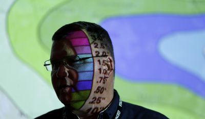 Weather data is projected on the face of Clint Perkins director of state operations for the Georgia Emergency Management as he works in the emergency operations center Tuesday, Feb. 11, 2014, in Atlanta.  Georgia is bracing for a winter storm. (AP Photo/John Bazemore)