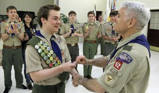 FILE - In this Feb. 10, 2014 fie photo Pascal Tessier, left, a gay Boy Scout, receives his Eagle Scout badge from Troop 52 Scoutmaster Don Beckham, right, in Chevy Chase, Md., to become one of the first openly gay scouts to reach scouting's highest rank. The Boy Scouts of America said Wednesday, Feb. 12, 2014 that it lost 6 percent of its membership after an often-bruising year in which it announced it would accept openly gay boys for the first time, over the objections of some participants who eventually left the organization. (AP Photo/Luis M. Alvarez, File)