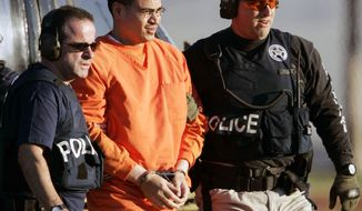 FILE - In this Jan. 5, 2006, file photo, Jose Padilla, center, is escorted by federal marshals on his arrival in Miami. Miami U.S. District Judge Marcia Cooke scheduled a Wednesday afternoon Feb. 12, 2014 hearing for Padilla. He originally was sentenced to 17 years of prison for terrorism support and conspiracy convictions. A federal appeals court ruled in 2011 that the sentence was too lenient, given Padilla's lengthy criminal record and terrorist training at an al-Qaida camp in Afghanistan.(AP Photo/Alan Diaz, File)