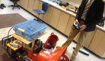 Wausau West High School senior Ethan Klein maneuvers the school's robot snowblower in Wausau, Wis. on Thursday, Feb. 6, 2014. He and his classmates are developing it through a grant from MIT and the Lemmelson Foundation. Klein and the rest of the team of 13 students working on the project hope to make it work autonomously. (AP Photo/The Wausau Daily Herald, Keith Uhlig)