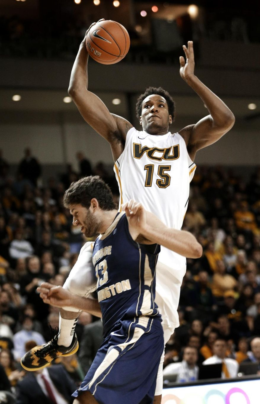 George Washington's Patricio Garino bumps VCU's Juvonte Reddic on a fast break during the first half of an NCAA college basketball game in Richmond, Va., on Wednesday, Feb. 12, 2014. Reddic dunks, and Garino was called for a foul. (AP Photo/ Richmond Times-Dispatch, Dean Hoffmeyer)