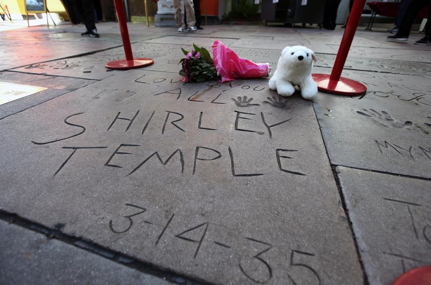 Flowers and a stuffed animal are left at the hand and foot prints for Shirley Temple Black at the TCL Chinese Theatre in the Hollywood section of Los Angeles on Tuesday, Feb. 11, 2014. Temple, who died Monday night at 85, sang, danced, sobbed and grinned her way into the hearts of Depression-era moviegoers and remains the ultimate child star decades later. (AP Photo/Richard Vogel)
