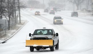 A snow plow travels on Pelham Rd. on Wednesday, Feb. 12, 2014, in Greenville, S.C. Snow and icy conditions in the southeast were expected to continue through Wednesday and into Thursday morning. (AP Photo/Rainier Ehrhardt)