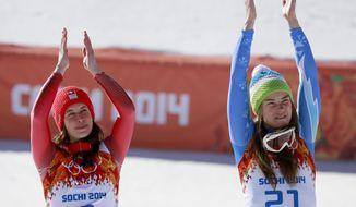Women's downhill gold medalists Switzerland's Dominique Gisin, left, and Slovenia's Tina Maze, right, applaud during a flower ceremony at the Sochi 2014 Winter Olympics, Wednesday, Feb. 12, 2014, in Krasnaya Polyana, Russia. (AP Photo/Gero Breloer)