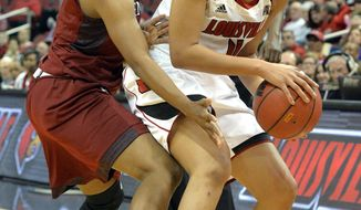 Louisville's Antonita Slaughter, right, looks to pass as Temple's Erica Coville defends during the first half of an NCAA college basketball game Wednesday, Feb. 12, 2014, in Louisville, Ky. (AP Photo/Timothy D. Easley)