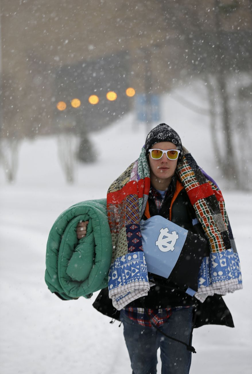 Breton Nicholas, a student at the University of North Carolina in Chapel Hill, N.C., walks outside the Dean E. Smith Center prior to a basketball game between North Carolina and Duke Wednesday, Feb. 12, 2014. Breton carries his friends belongings after waiting outside for tickets to tonight's game. The National Weather Service has issued a winter storm warning for Wednesday and into Thursday covering most of North Carolina. (AP Photo/Gerry Broome)