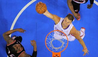 Los Angeles Clippers forward Blake Griffin goes up for a dunk as Portland Trail Blazers forward LaMarcus Aldridge watches during the first half of an NBA basketball game, Wednesday, Feb. 12, 2014, in Los Angeles. (AP Photo/Mark J. Terrill)