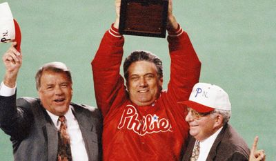 **FILE** Philadelphia Phillies manager Jim Fregosi, center, holds up the NL Championship trophy as Phillies general Manager Lee Thomas, left, and Phillies President Bill Giles look on during their drive around the field after the Phillies 6-3 win over the Atlanta Braves in Game 6 of the NL Playoffs, Oct. 14, 1993, Philadelphia, Pa. (AP Photo/George Widman)