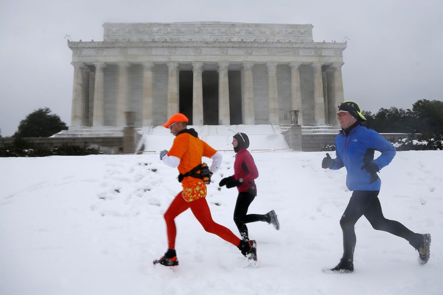 From  left, Alejandro Escobar, Courtney Fulton, and Trevor Albert, all from Arlington, Va., run in the snow past the Lincoln Memorial in Washington, Thursday, Feb. 13, 2014. After pummeling wide swaths of the South, a winter storm dumped nearly a foot of snow in Washington as it marched Northeast and threatened more power outages, traffic headaches and widespread closures for millions of residents. (AP Photo/Charles Dharapak)