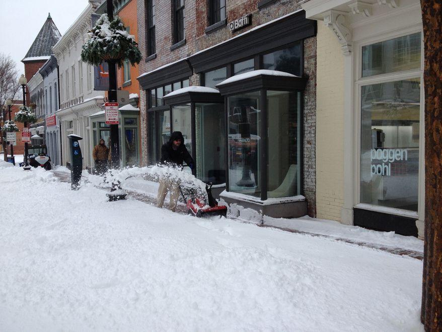 ** FILE ** A man clears the sidewalk with a snow blower on M Street NW in Washington, D.C., on Feb. 13, 2014. (Lloyd Villas/The Washington Times)