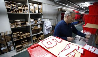 Washington Nationals equipment manager Mike Wallace works in the equipment room at their spring training baseball facility, Thursday, Feb. 13, 2014, in VIera, Fla. (AP Photo/Alex Brandon)