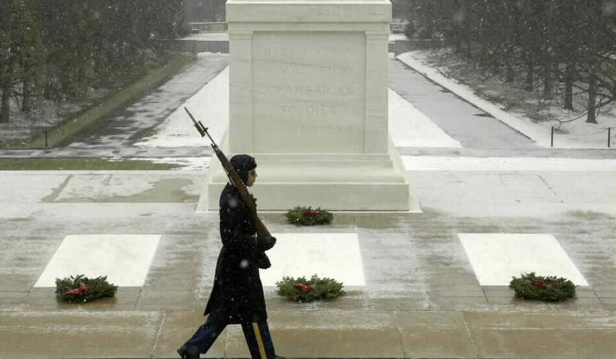 A sentinel at the Tomb of the Unknown Soldier stands guard amid falling snow. (Defense Department photo) **FILE**