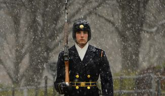 Spc. Jacob Davenport, Sentinel, Tomb of the Unknown Soldier, 3d U.S. Infantry Regiment (The Old Guard), walks his 21 steps as the snow starts falling at the Tomb of the Unknown Soldier at Arlington National Cemetery, Va. (Army photo)