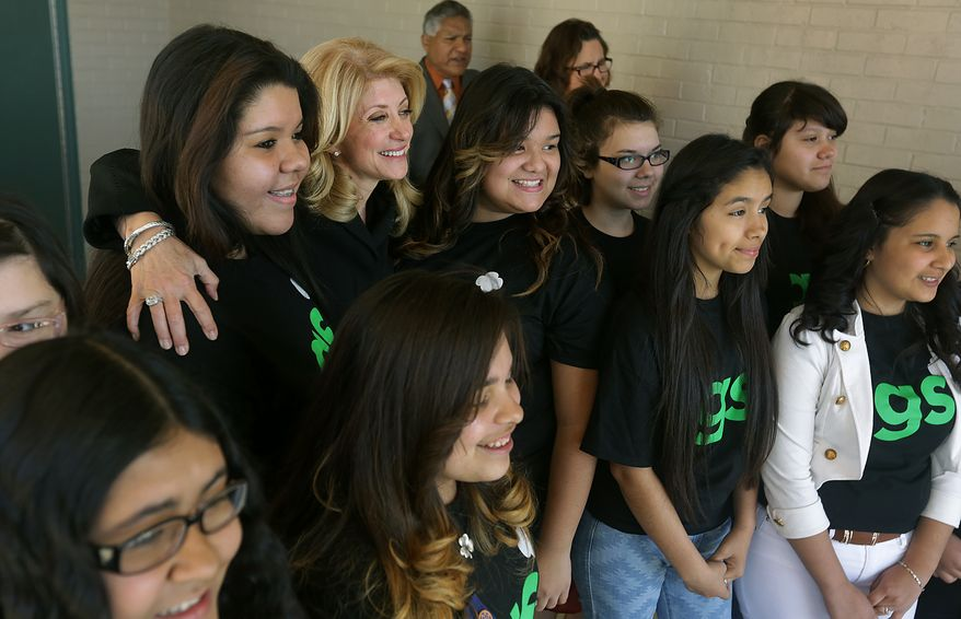 State Sen. Wendy Davis, second from left, Democratic candidate for governor, poses with 8th grade Girl Scouts from Leal Middle School during a visit on Thursday to discuss her proposal to improve early childhood education. Thursday, Feb. 13, 2014.  (AP Photo/San Antonio Express-News, Bob Owen)