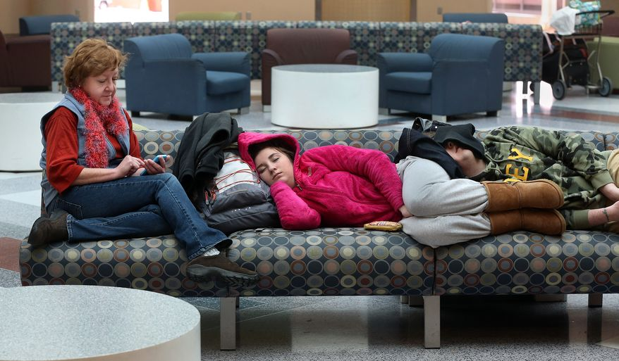 """Janie Funai, left, of Mechanicsville, Va., plays """"Candy Crush"""" on her phone while waiting with her children Emma, 16, center, and Ben, 25, for a flight at Richmond International Airport, Thursday.  Feb. 13, 2014. They arrived around 5 a.m. with Ben to catch a 6:55 a.m. flight which was canceled.   They were waiting to board a flight to Charlotte, N.C.  Ben is on his way to Las Vegas to see a performance by Britney Spears. (AP Photo/Richmond Times-Dispatch, P. Kevin Morley)"""