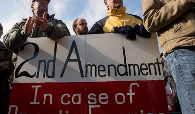 Jay Hanlon of Silver Spring, Md., second from left, and Mike Toeneboehn  of Annapolis, Md., second from right, hold a 2nd amendment sign as they listen to speakers at at a pro-gun rights rally against a proposal by Maryland Governor Martin O'Malley that would ban assault weapons and require residents to obtain a license before purchasing handguns at Lawyers Park in front of the Maryland State House, Annapolis, Md., Wednesday, February 6, 2013. (Andrew Harnik/The Washington Times)