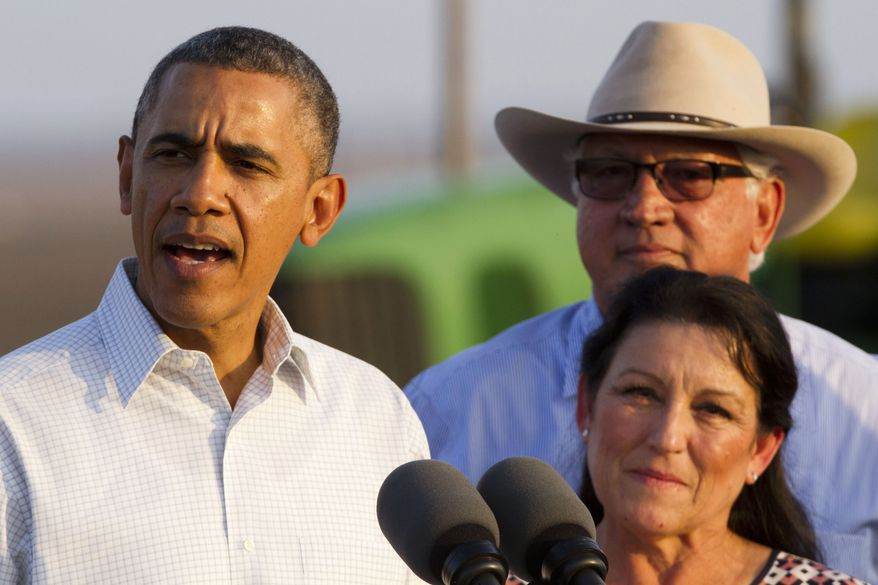 President Barack Obama speaks about drought on a local farm with Joe Del Bosque,  right, and Maria Gloria Del Bosque, of Empresas Del Bosque, Inc., in Los Banos, Calif., Friday, Feb. 14, 2014.  (AP Photo/Jacquelyn Martin)