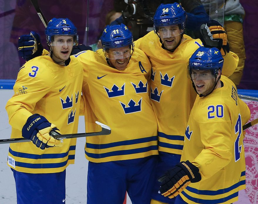 Sweden forward Daniel Alfredsson, second from left, celebrates with teammates after scoring a goal against Switzerland in the third period of a men's ice hockey game at the 2014 Winter Olympics, Friday, Feb. 14, 2014, in Sochi, Russia. (AP Photo/Julio Cortez)