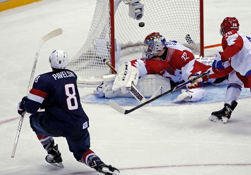 USA forward Joe Pavelski (8) scores against Russia goaltender Sergei Bobrovski in the third period of a men's ice hockey game at the 2014 Winter Olympics, Saturday, Feb. 15, 2014, in Sochi, Russia. (AP Photo/Petr David Josek)