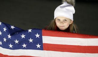 A young fan with an American flag waits for the start of the men's two-man bobsled competition at the 2014 Winter Olympics, Sunday, Feb. 16, 2014, in Krasnaya Polyana, Russia. (AP Photo/Natacha Pisarenko)