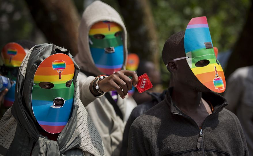 """FILE - In a Monday, Feb. 10, 2014 file photo, Kenyan gays and lesbians and others supporting their cause wear masks to preserve their anonymity and one holds out a wrapped condom, as they stage a rare protest, against Uganda's increasingly tough stance against homosexuality in solidarity with their counterparts there, outside the Uganda High Commission in Nairobi, Kenya. President Barack Obama says in a statement provided Sunday, Feb. 15, 2014 that pending steps by Uganda to further criminalize homosexuality will complicate what he is describing as America's valued relationship with the East African nation. Museveni said Friday that he plans to sign a bill into law that prescribes life imprisonment for what they term as """"aggravated"""" homosexual acts.(AP Photo/Ben Curtis)"""