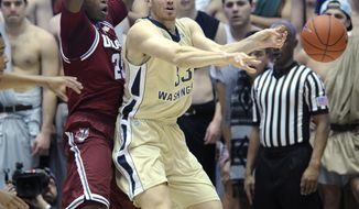 George Washington forward Paris Maragkos (33) passes the ball under pressure from Massachusetts forward Cady Lalanne (25) during the first half of an NCAA college basketball game at the Smith Center in Washington, Saturday, Feb. 15, 2014. (AP Photo/Susan Walsh)